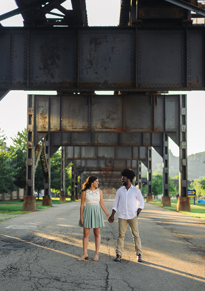 Couple looking at each other smiling under a bridge while sun shines behind