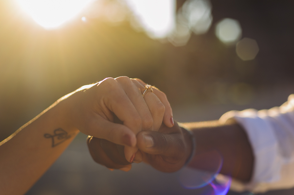portrait of couple hands while the sun shines behind gently
