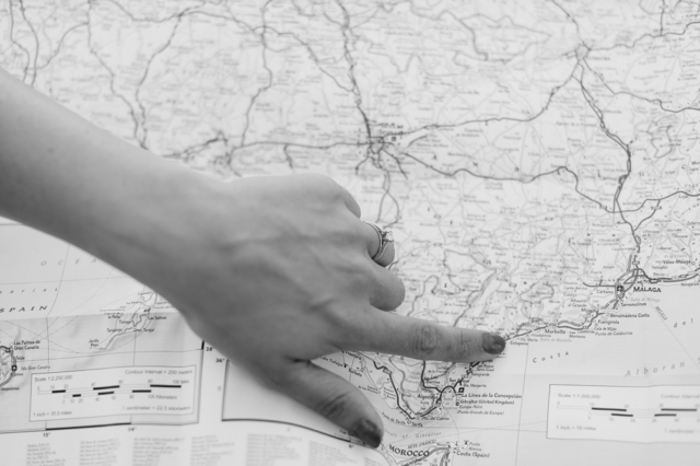 girl showing her engagement ring while pointing to a map