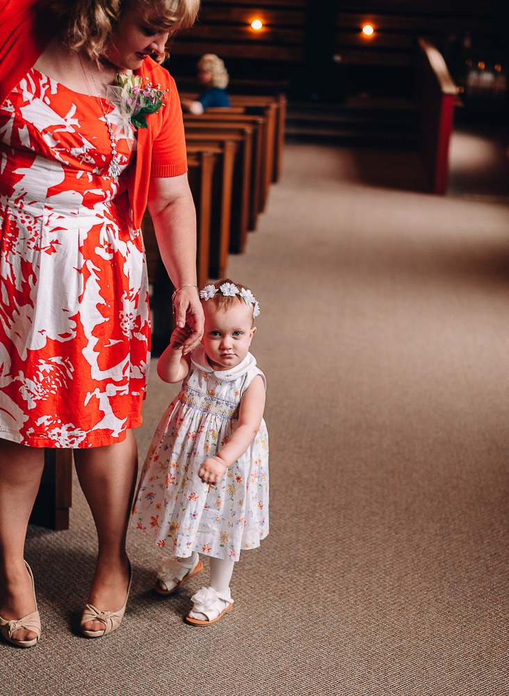 Flower girl holding mom's hands while looking at camera