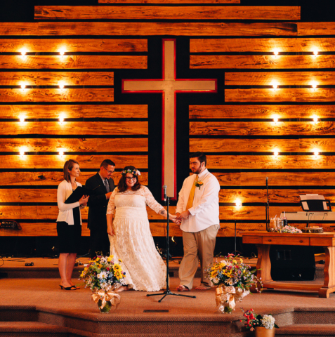 Bride and groom holding hands in front of cross during wedding ceremony