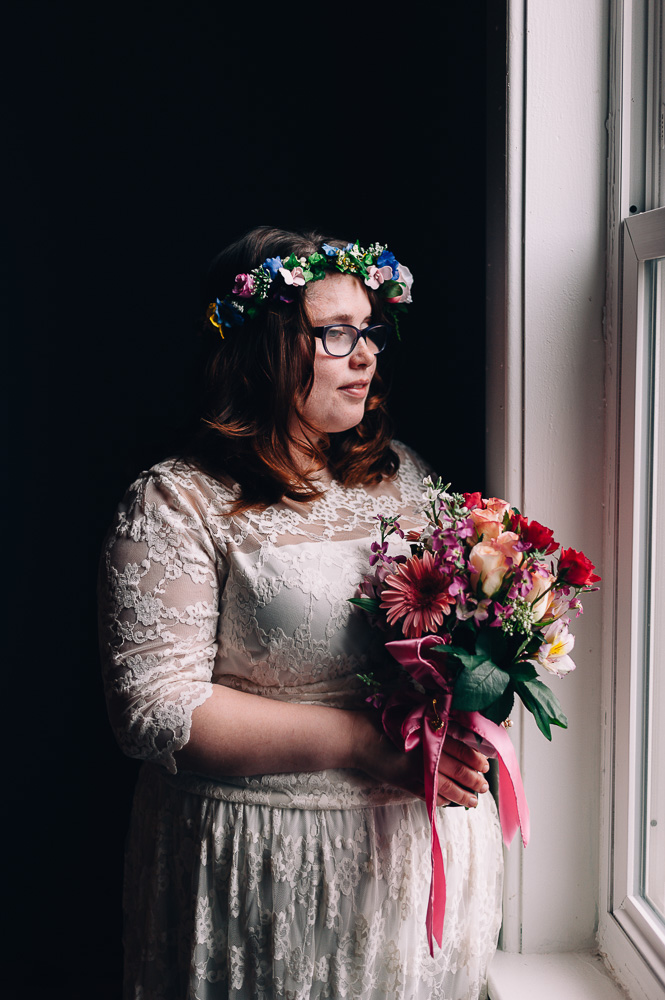 Moody Portrait of Hipster bride looking at window
