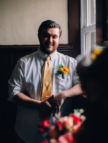 moody portrait of hipster groom next to window