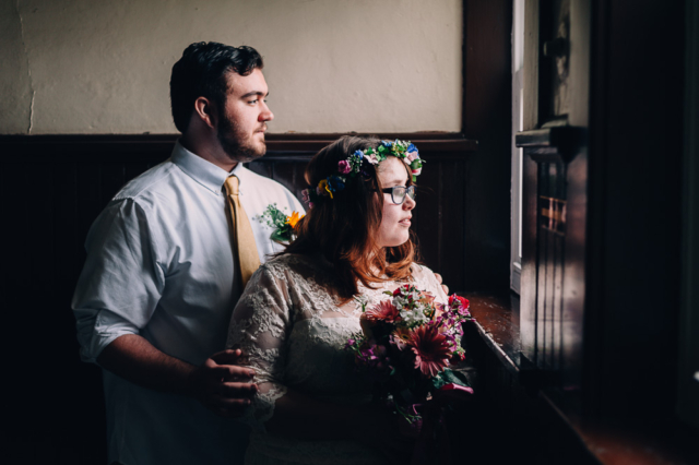 Moody Portrait of groom and bride by the window