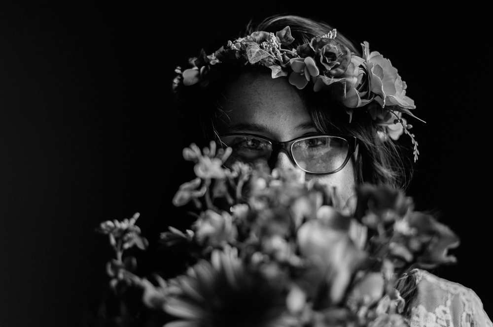 Black and White portrait of hipster bride looking at camera while hiding behind bouquet