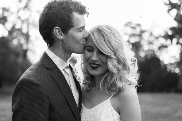 Black and White Portrait of husband kissing wife