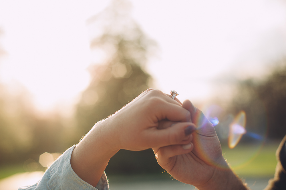 Engaged couple holding hands showing engagement ring while sun shines gently through