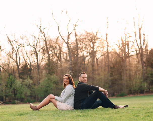 Couple sitting down on the grass looking at the camera as the sunset shines behind them