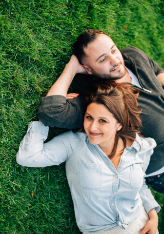 man and woman laying on the grass while woman looks at the camera smiling