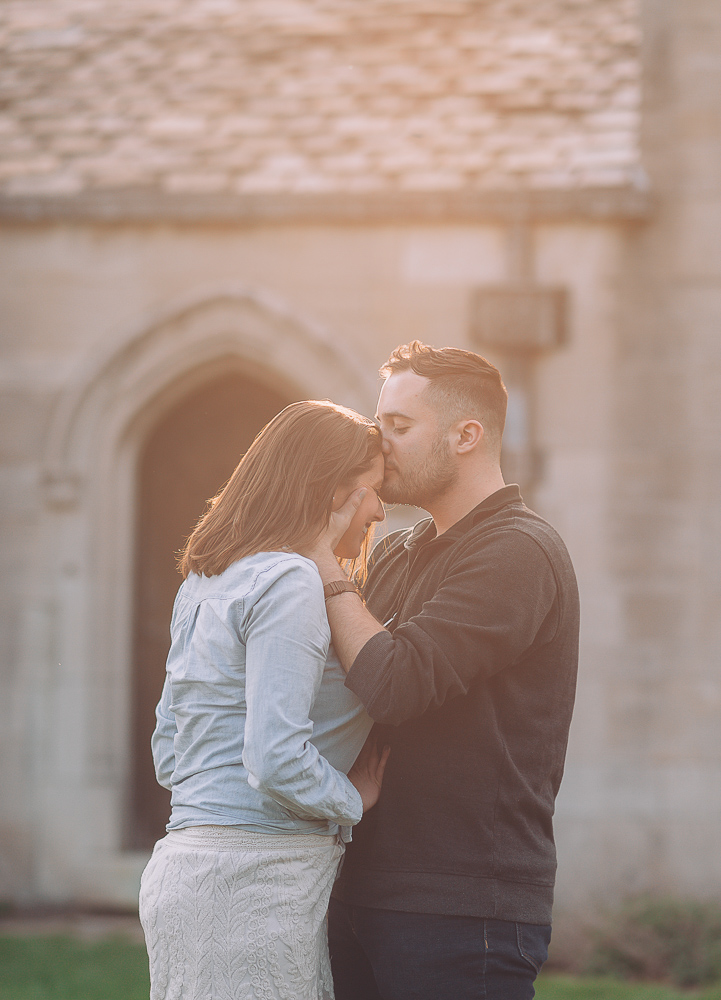 Portrait of man kissing woman while the sun shines
