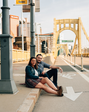 Couple sitting looking at the camera while Clemente Bridge is in back