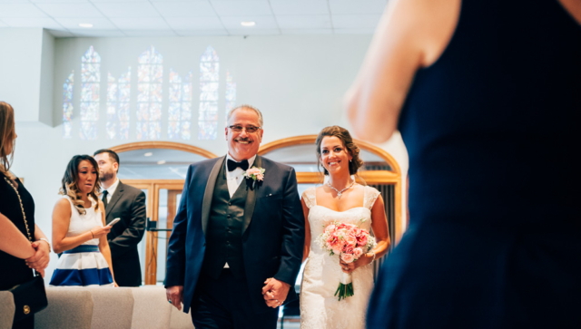 father escorting bride down the aisle during wedding ceremony