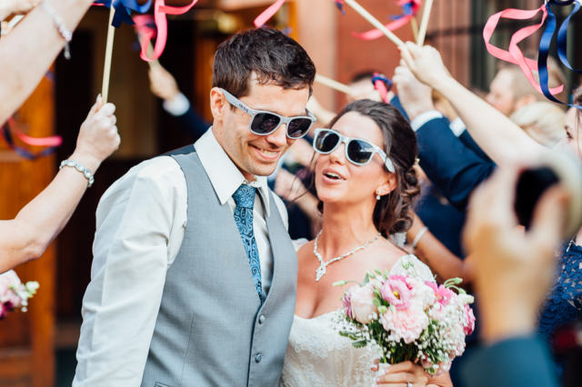 bride and groom wearing sunglasses during flag exit after ceremony