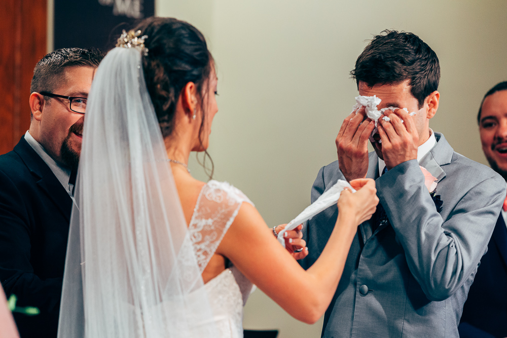 bride hands groom a tissue as he cries after seeing her