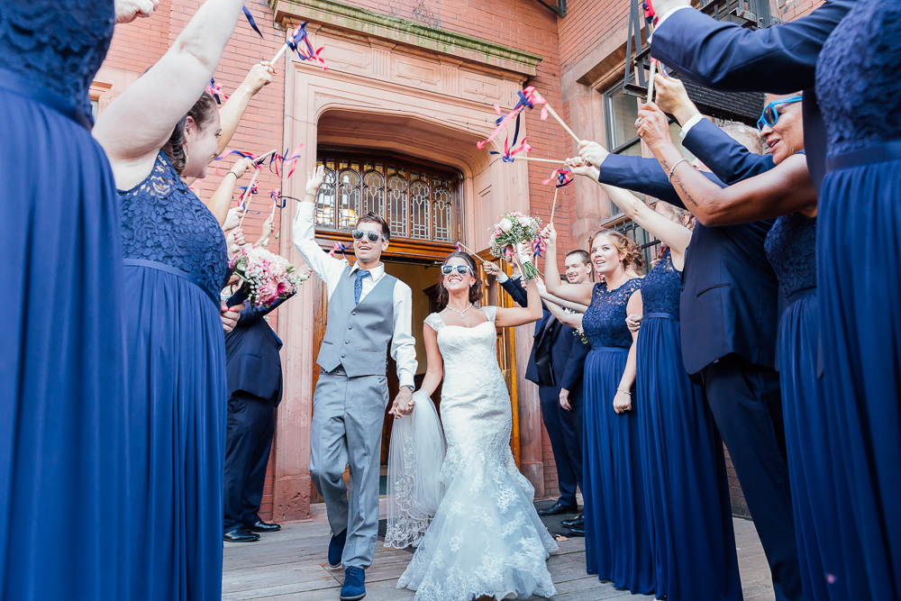 bride and groom walking during flag exit after wedding ceremony