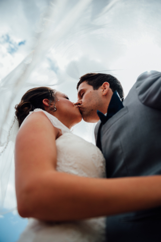 bride and groom kissing as veil falls on them from above