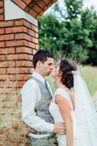 newly married couple kissing while leaning on column