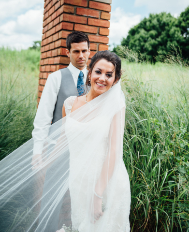 portrait of newly married bride looking at camera smiling as groom looks on