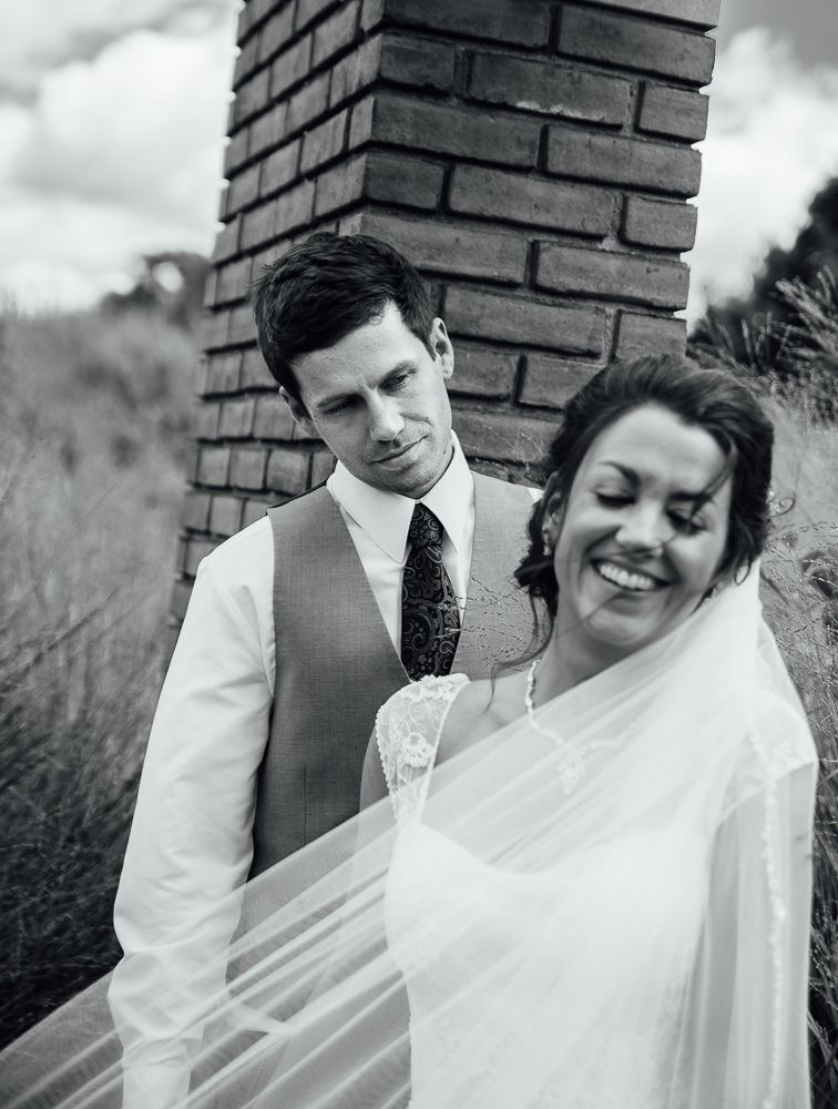black and white portrait of groom looking on bride happily