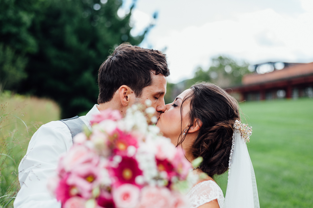 newly married couple kissing behind bouquet