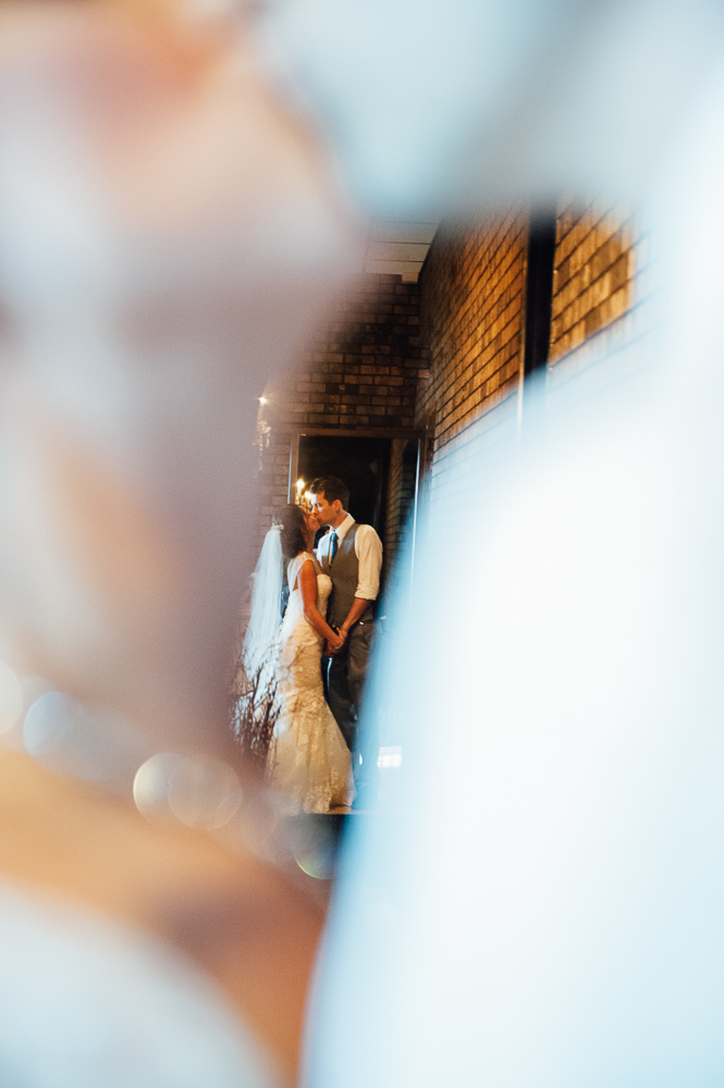 bride and groom kiss in front of mirror