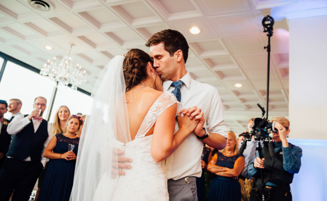 groom kissing his bride as they dance for the first time as a married couple