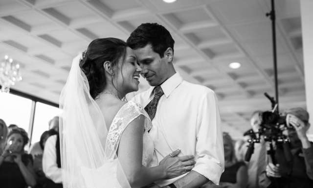 bride smiling as she dances with groom