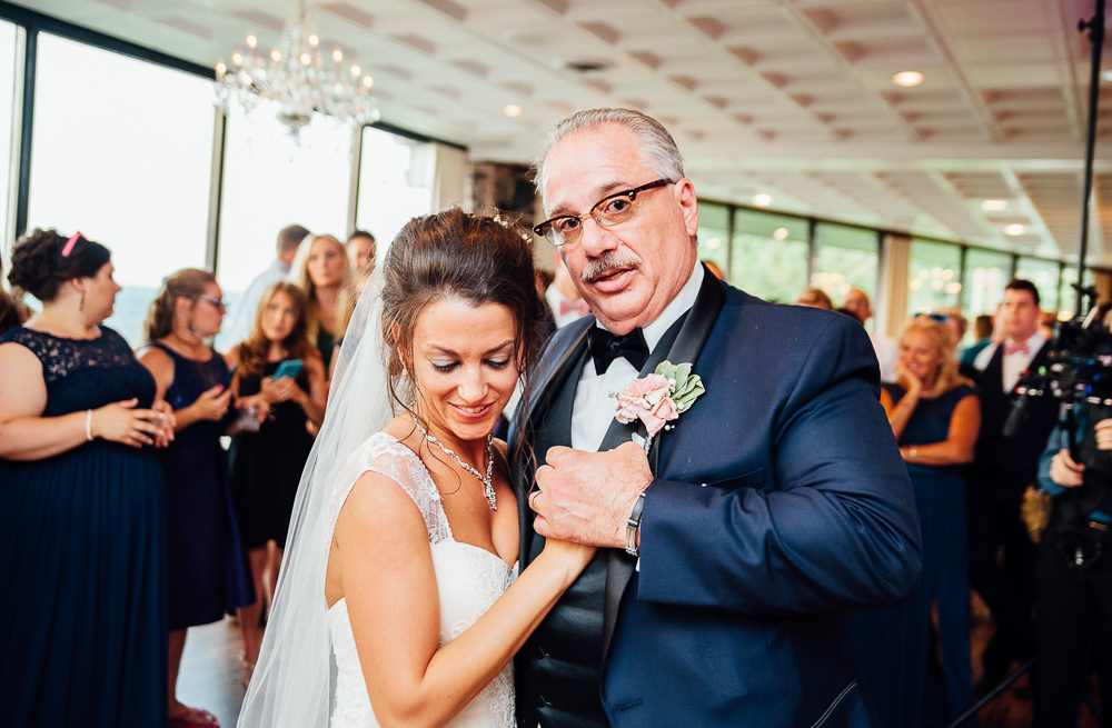father of the bride looks at camera as he dances with bride