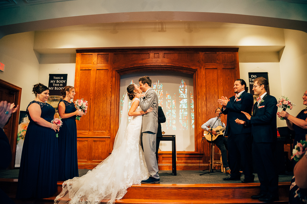 bride and groom kiss for the first time as wedding party looks on them happy